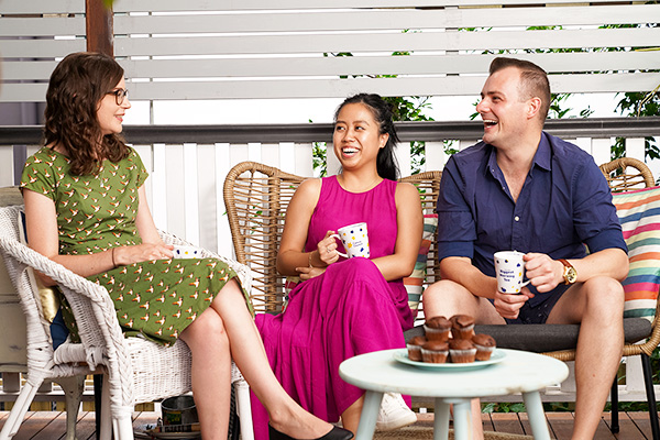 Three people drinking tea on a verandah around a table with a plate of chocolate muffins
